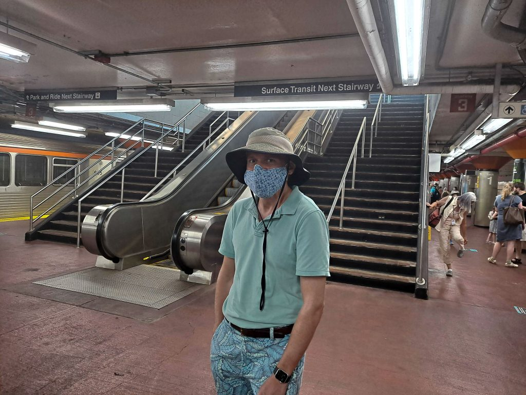 Collin Sundt wears a face mask while standing at the bottom of an escalator