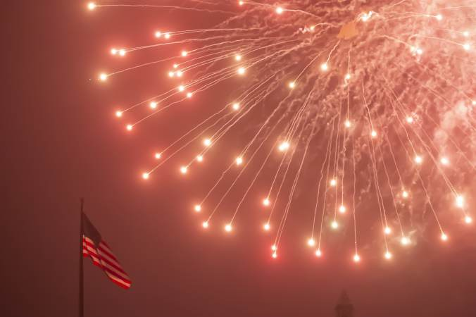 An American flag flutters as fireworks rain down during the July Fourth fireworks display at the Philadelphia Museum of Art. (Jonathan Wilson for WHYY)