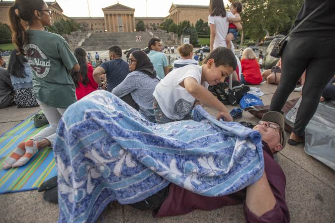 On Eakins Oval, a rambunctious Taaya Wittenmeyer, 9, covers his father, Brian Wittenmyer with a blanket during the family's nearly 3 hour wait for the fireworks display at the Philadelphia Museum of Art. His family, from Ashburn VA was visiting Philadelphia over the Fourth of July weekend. (Jonathan Wilson for WHYY)
