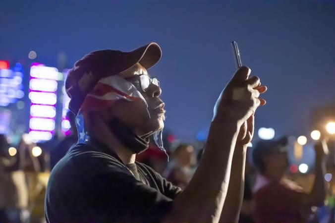 On Eakins Oval Donald Dennison using his phone records the July Fouth fireworks display. (Jonathan Wilson for WHYY)