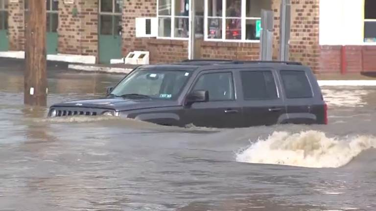 Aa car is pictured in heavy floodwaters