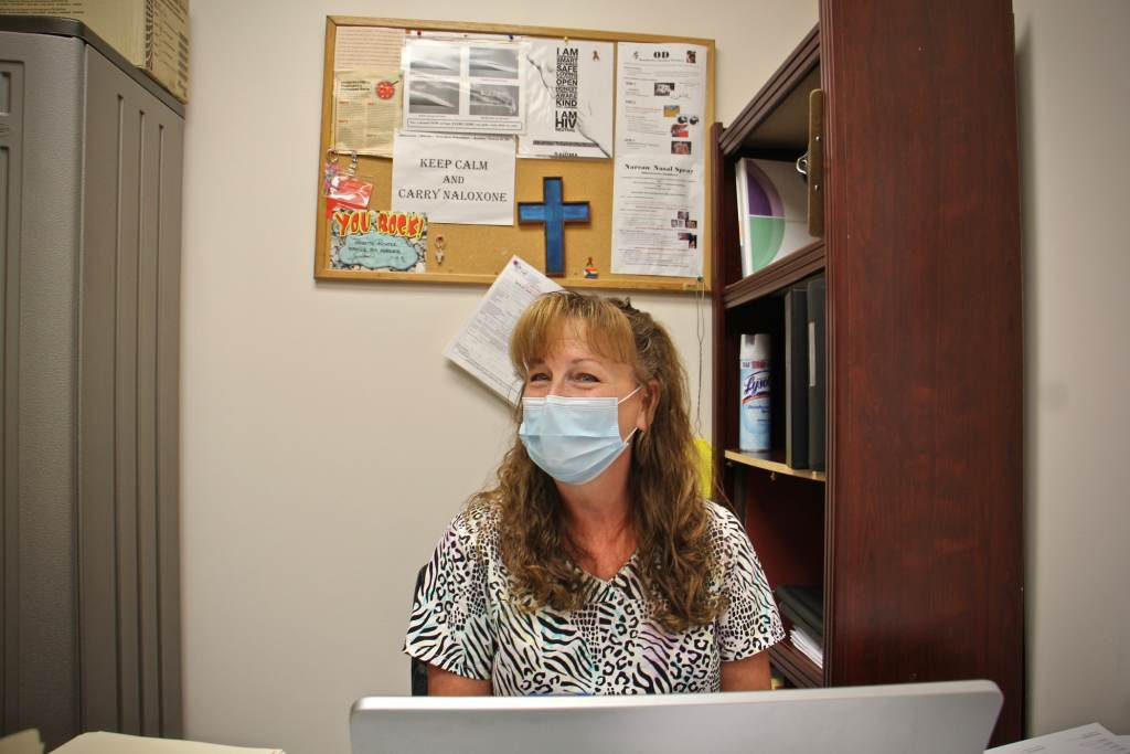 Babette Richter sits at a desk while wearing a mask