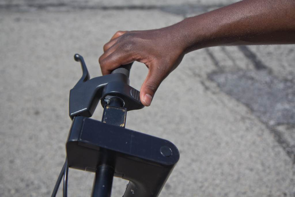 A closeup of a person's hand on a Verve S pedal bike handle