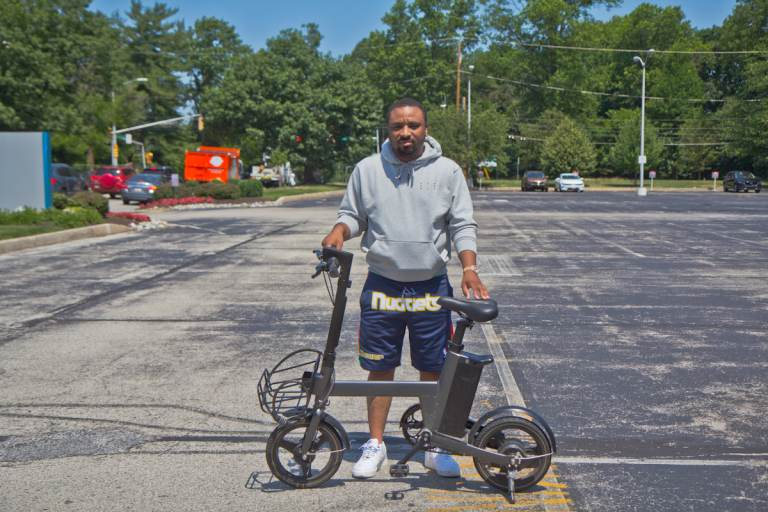 Kevin Thompson stands outside with a Verve S pedal bike