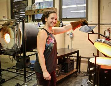 Danielle Ruttenberg, co-owner of Remark Glass, opens an oven in her studio in the basement of the Bok Building in South Philadelphia. (Emma Lee/WHYY)