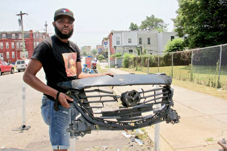De'Wayne Drummond picks up a grill left behind after a crash at 34th Street and Mantua Avenue