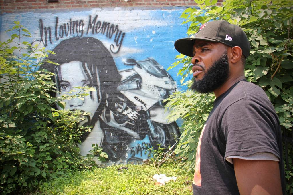 De'Wayne Drummond stands beside a mural dedicated to a motorcyclist who was killed at the intersection of 34th Street and Haverford Avenue