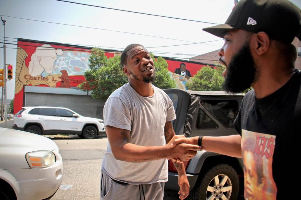 Forrest Carroll (left) and De'Wayne Drummon shake hands outside