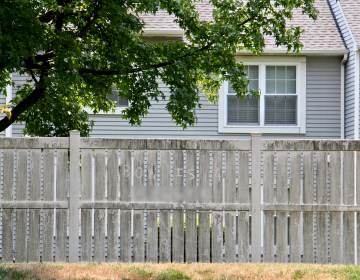 A racial slur etched into the dirt on a privacy fence at the Essex condominium complex in Mount Laurel, N.J., appears to be directed at Ron Howard, president of the homeowners association. (Emma Lee/WHYY)