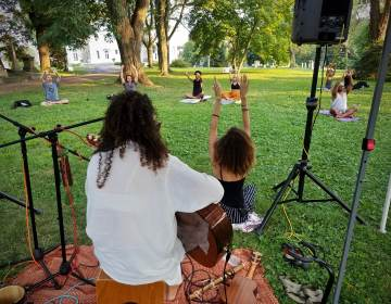 Aubrey Howard (in black tank) leads a session of intentional breathing meditation, accompanied by musician Alexia Oliveira, during a yoga session at the Woodlands cemetery. (Peter Crimmins/WHYY)
