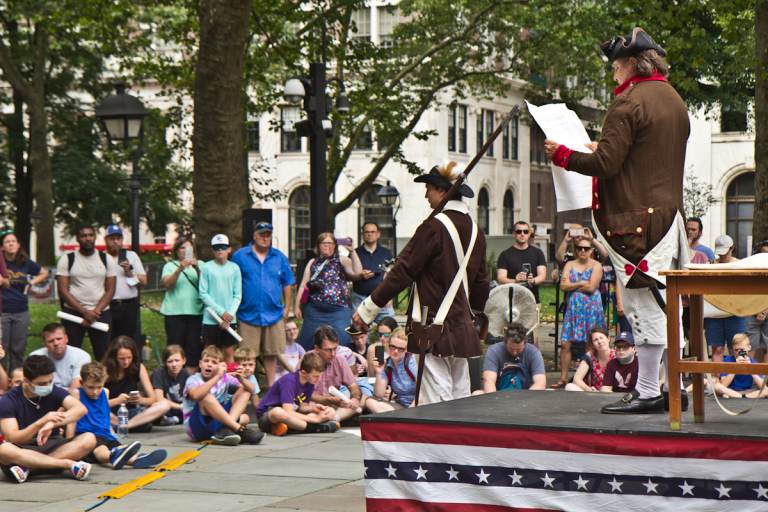 Actors perform a reading of the Declaration of Independence at Independence Hall as spectators watch