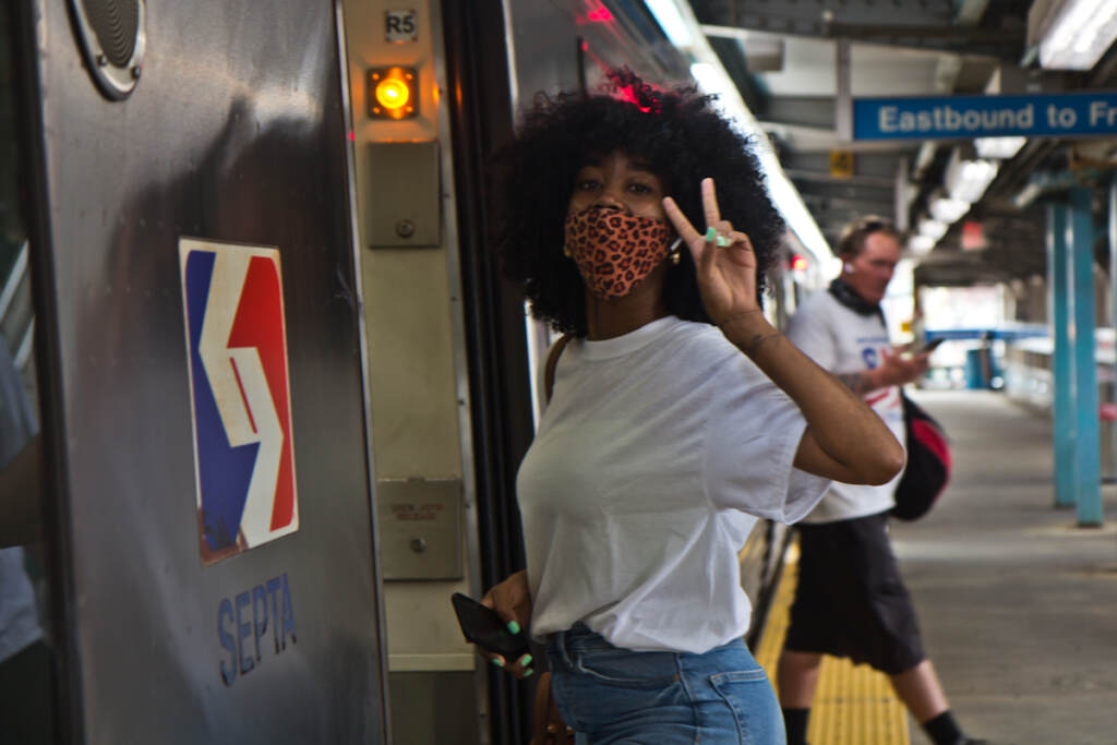 Tykira Octavia throws up a peace sign as she boards a Market-Frankford Line train