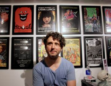 Eric Bresler sits in front of a series of posters
