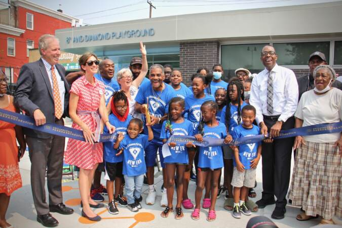 Dana Clark (center), surrounded by children, cuts the ribbon for the reopening of the rebuilt 8th and Diamond Playground,
