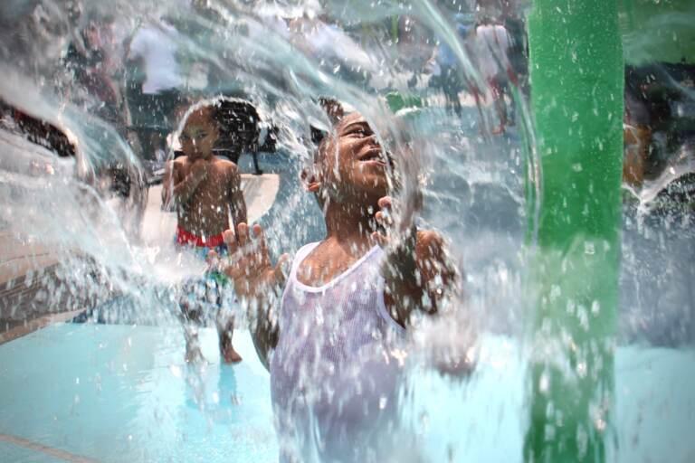 Mesiah Clark splashes around at a sprayground in Philly
