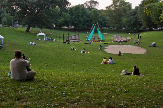 People sit outside at Clark Park to watch a Shakespeare play