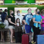 People wait in line to rent vehicles at Miami International Airport Friday, May 28, 2021, in Miami. The shortage of rental vehicles will cause long delays and higher prices thought the summer. (AP Photo/Marta Lavandier)