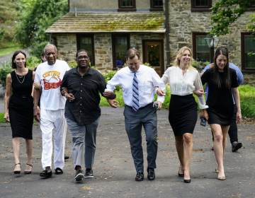 Bill Cosby, second left, and spokesperson Andrew Wyatt, third left, approach members of the media gathered outside Cosby's home in Elkins Park, Pa., Wednesday, June 30, 2021, after Pennsylvania's highest court overturned his sex assault conviction. (AP Photo/Matt Rourke)