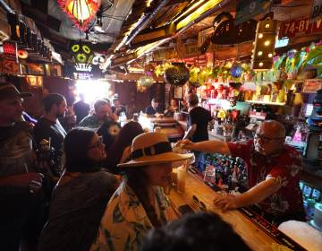 FILE - In this Wednesday, July 7, 2021, file photo, patrons enjoy cold tropical cocktails in the tiny interior of the Tiki-Ti bar as it reopens on Sunset Boulevard in Los Angeles. COVID-19 cases have doubled over the past three weeks, driven by the fast-spreading delta variant, lagging vaccination rates in some states and Fourth of July gatherings.  Los Angeles County public health officials have urged people to resume wearing masks indoors regardless of their vaccination status. (AP Photo/Damian Dovarganes, File)