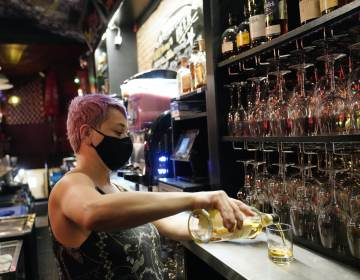 Erin Bellard pours a drink for a customer at her bar