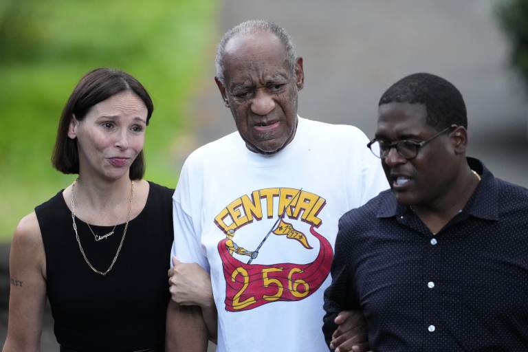 Bill Cosby, center, and spokesperson Andrew Wyatt, right, approach members of the media