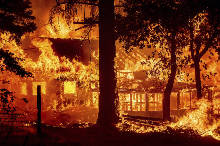 Flames from the Dixie Fire consume a home in the Indian Falls community