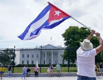 A person flies a Cuban flag outside the White House