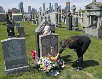 Sharon Rivera adjusts flowers and other items left at the grave of her daughter, Victoria