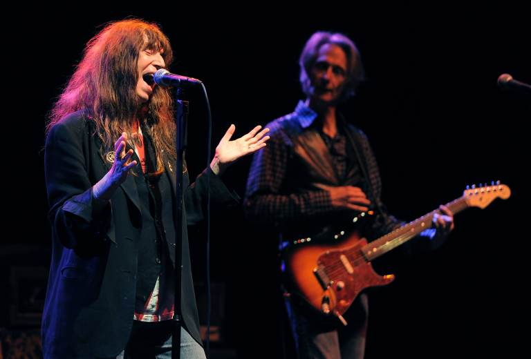 Patti Smith performs onstage, with a guitarist to her left
