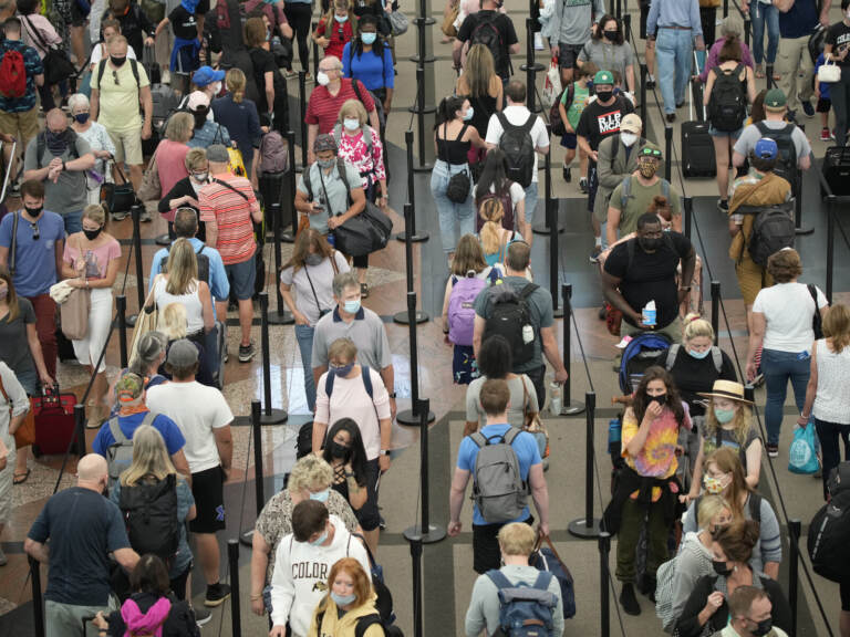 Travelers queue up in long lines to pass through an airport security checkpoint