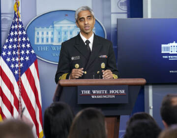 Surgeon General Dr. Vivek Murthy speaks from a podium at the White House briefing room