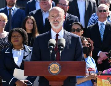 Gov. Tom Wolf speaks from a podium with people behind him