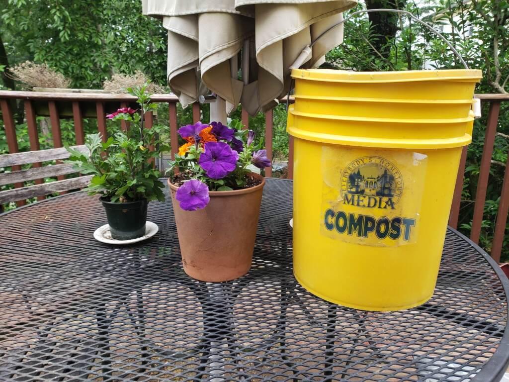 A flower pot sits next to a Media compost bucket.