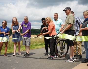 Burlington County officials and representatives from partnering organizations cut the ribbon on the new Delaware River Heritage Trail Bypass 130. (Kenny Cooper/WHYY)