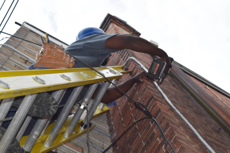 Worker replacing main electrical service line into home as part of Basic Systems Repair Program. (Courtesy PHDC)