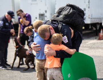 Brandon Watkins, a member of PA-Task Force 1, hugs his kids, Nicholas, 5, and Jackson, 7, in Philadelphia on July 16, 2021, after he returned from assisting in the search and recuse mission in Surfside City, Florida. (Kimberly Paynter/WHYY)