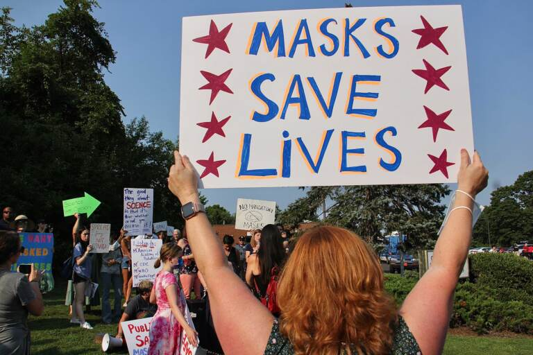 Parents gather outside a Central Bucks school board meeting to protest or defend the board's decision to open schools in the fall without requiring protective face masks. (Emma Lee/WHYY)