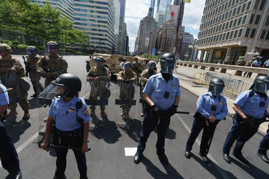 Philadelphia police and National Guard members stand on a Philly street