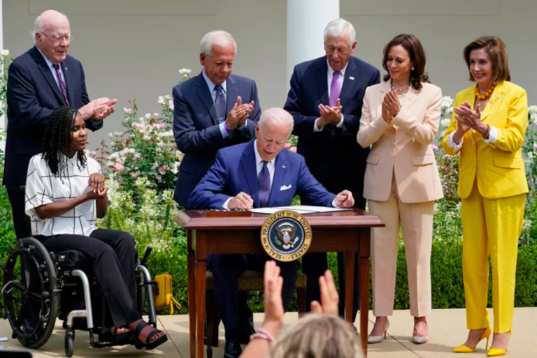 President Joe Biden, center, signs a proclamation during an event in the Rose Garden of the White House in Washington, Monday, July 26, 2021, to highlight the bipartisan roots of the Americans with Disabilities Act. (Susan Walsh/AP)