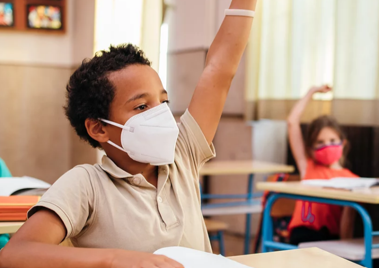 A masked student raises his hand in class.
