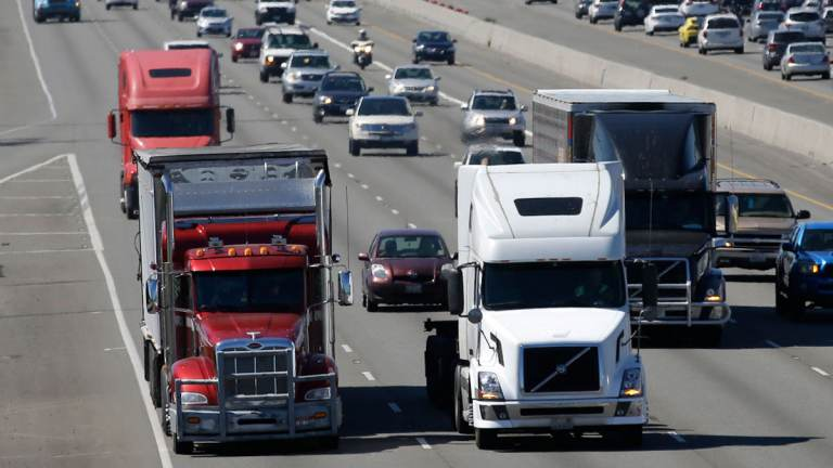 Trucks and cars travel down the highway.