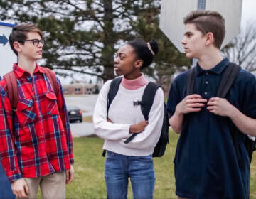 Two teenage boys and a teenage girl talking outside of school