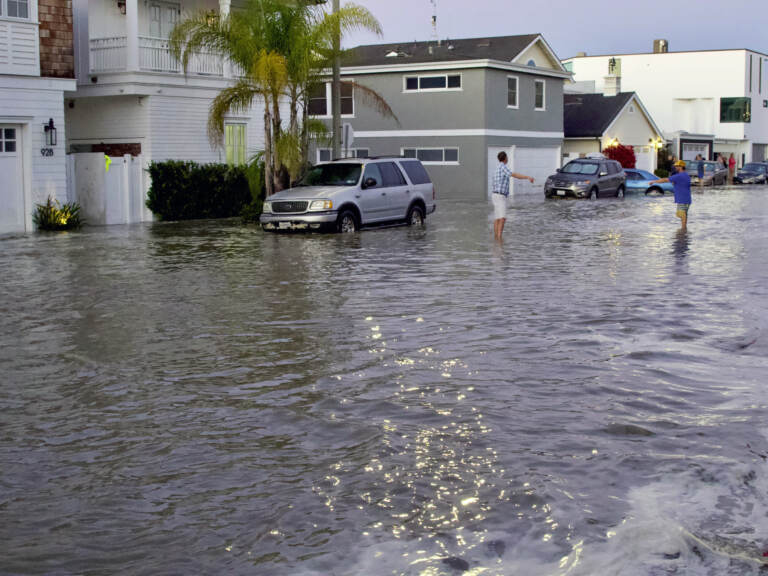 Streets and homes flooded in Newport Beach, Calif., during a high tide in July 2020. So-called sunny day floods are getting more common in coastal cities and towns as sea levels rise due to climate change. (Matt Hartman/AP)