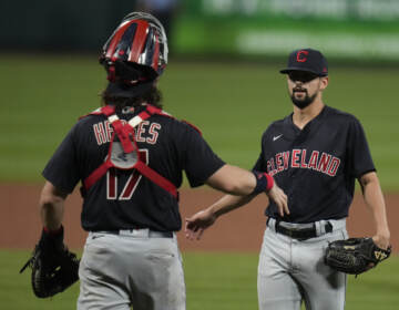 Cleveland relief pitcher Nick Sandlin (right) and catcher Austin Hedges celebrate a 10-1 victory over the St. Louis Cardinals on June 8, 2021, in St. Louis. On Friday, the Cleveland team announced its new name, the Guardians. (Jeff Roberson/AP)