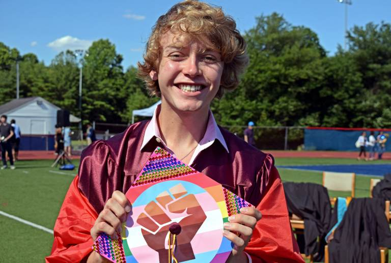 Bryce Dershem holds up his graduation cap, which features a fist on top of a trans pride flag