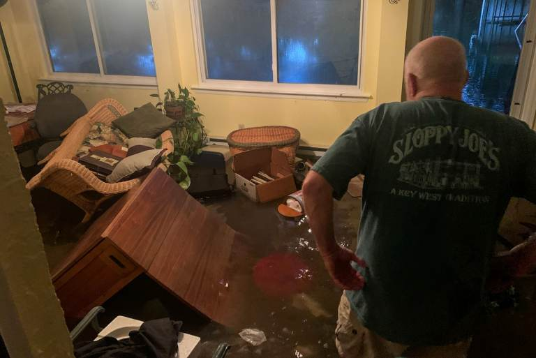 A Bucks County resident observes the aftermath of flooding at his residence.