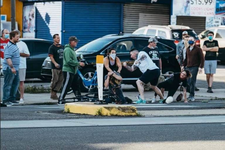 A group of people attack a man who has been knocked off his bike