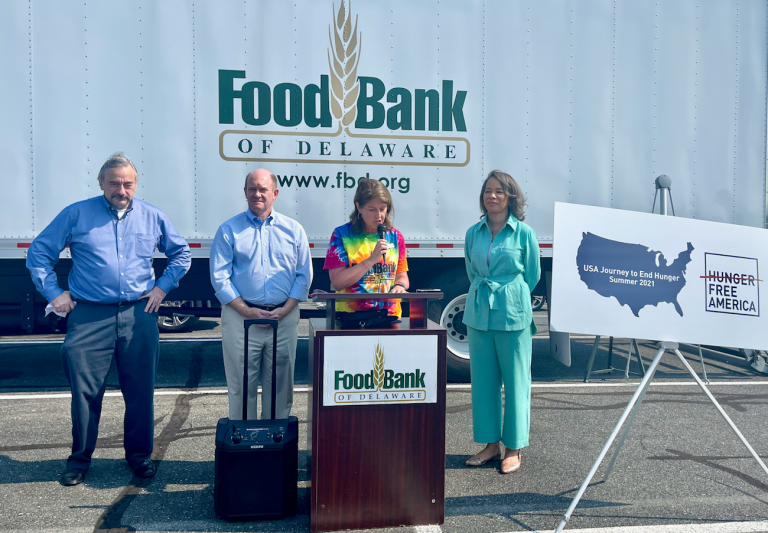 Hunger Free America CEO Joel Berg (left) joins U.S. Sen. Chris Coons, Food Bank of Delaware president Cathy Kanefsky and Delaware Congresswoman Lisa Blunt Rochester at a food distribution event in Georgetown Tuesday morning. (Johnny Perez-Gonzalez / WHYY)