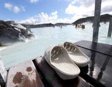 A pair of sandals are pictured in the foreground, with Blue Lagoon in the background