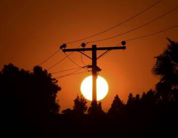 The sun sets behind power lines in Los Angeles in September. (Frederic J. Brown/AFP via Getty Images)
